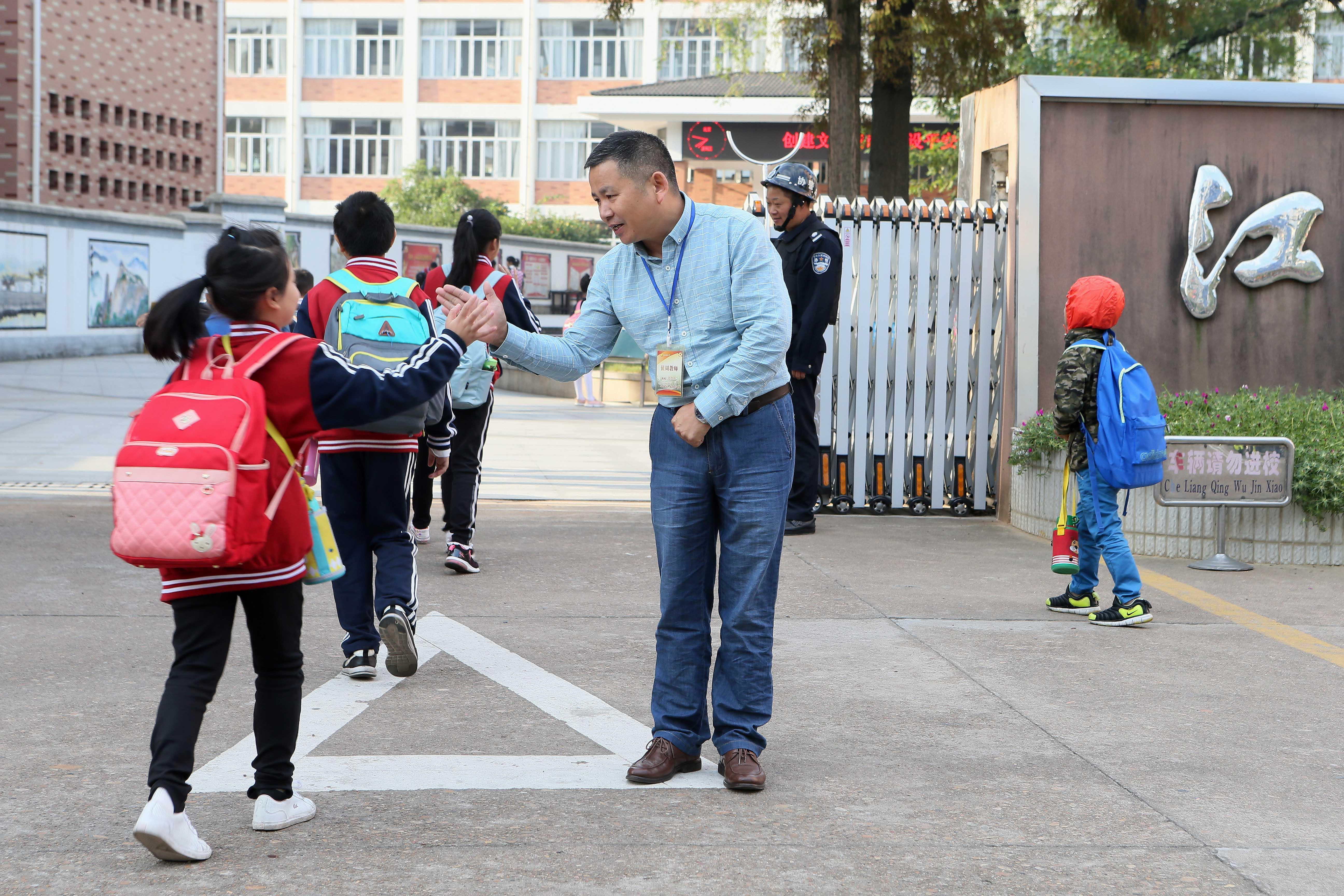 浙江江山一小学校长在校门口迎学生 坚持十年不间断